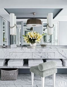 Hervé Van der Straeten sconces overlook a master baths marble vanity. The stool is covered in terry cloth.