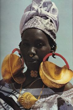 Earmarks of wealth among the Fulanis, giant gold ornaments festoon a woman at Dialloube; a head strap often helps support the heavy earrings. As a family's fortunes increase, more gold may be hammered onto the jewelry. Filigree, often found along the Niger, dates to the time when West African monarchs cornered the bulk of the continent's known gold supply.