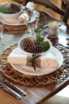 A rustic but elegant setting, twigs, fresh greenery, and pinecones are paired with clean white china, silver, and crystal.