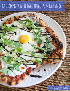 Grilled pizza with egg, arugula, and balsamic