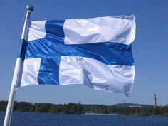 The Finnish flag by Juha K. | ... on a boat cruising on lake Kallavesi. Under the flag can be seen the city of Kuopio. - https://www.flickr.com/photos/jmk1112/1458403005/