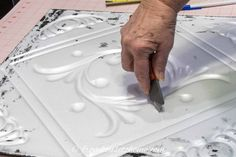 Utility knife cutting a hole in a styrofoam ceiling tile Styrofoam Ceiling Tiles, Faux Tin Ceiling Tiles, Morton Building Homes, Covering Popcorn Ceiling, Light Fixture Covers, Ceiling Installation, Dropped Ceiling, Painted Trays, Ceiling Light Fixtures