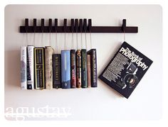 Very cool. The books sit on a little wooden block at the bottom of the strings, the pin at the top of the strings hang from the strip of wood.    Custom made wooden book rack by OldAndCold, $210.00