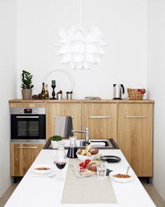 Dlouhý kuchyňský ostrůvek maximálně využívá místo v této úzké kuchyni