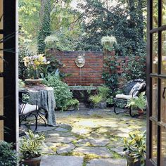 A brick-wall fence that bisects a side yard creates a backdrop for a courtyard garden w/ fountain, mossy rock floor + bistro table to eat breakfast on nice mornings. Make use of every scenic view - or create one. Southern Living