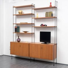 This Omnia modular teak wall unit was made by Hilker. It features black metal ladders with seven shelves and two cabinets with lockable double doors and a shelf each. The unit is veneered in teak.