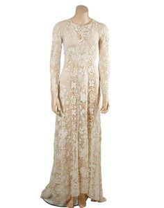 Irish White Crochet Lace Wedding Dress   Circa 1910   Central panel with serpentine floral pattern radiates from later empire construction and continues around skirt as do two flanking geometric borders widening out to a train, long sleeve