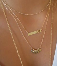 Dainty layered gold necklace set.