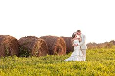Couple in field with round bales.