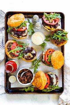 Fire up the grill! This crazy-delicious cheeseburger is fully loaded with a perfectly seasoned beef patty topped with creamy Cambozola blue cheese roasted garlic aioli, caramelized onions, fresh arugula, thick slices of tomatoes and bacon jam! This is how a burger should be made. #cheeseburger #baconcheeseburger #bluecheeseburger #burger #burgerrecipes #burgerideas #glutenfree