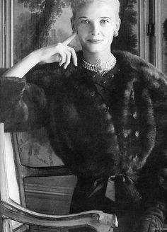 """CZ Guest is wearing a Tiffany necklace by Jean Schlumberger with a gray flannel dress and ranch-mink waist length """"barrel"""" jacket, both by Mainbocher, photo by Stephen Colhoun, Town & Country, Dec. 1956"""
