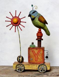 Folk art assemblage sculpture by Greg Guedel. Carved wood bird and found objects.