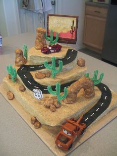 Cars Cake - I made this cake for my son's 5th birthday.  It was really fun!  White choc. cakes with strawberry filling. They are a half sheet, 10 in square, and 8 in round carved to look like a desert mountainside and covered in crushed nilla wafers and graham crackers. The cactus and signs are made of royal icing and the signs are handpainted with food color.  The rocks and road are fondant and the rock formations were rice krispie treats covered in fondant and sponge painted.