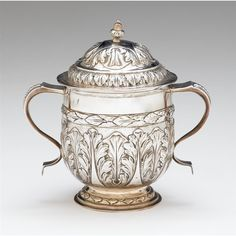 George I Britannia silver caudle cup with cover London, early 18th century Typical form, the lower body with repoussé and chased acanthus leaves, with twin S-scroll handles, raised on stepped circular foot, the cover similarly decorated with leaf motif, maker's mark rubbed.
