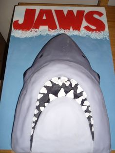 Jaws / Shark Cake made with a slab cake cut to shape, the mouth was moulded with the bits cut off. I then covered with 3 different shades...