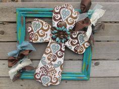 "A cream wooden Cross painted with swirl patterns in browns and blues sits off to the side of a turquoise wooden frame with splashes of orange and yellow. In the center of the Cross sits a metal flower painted in chocolate brown and turquoise. Ties of cream and blue burlap and ties of different wire ribbon surrounds this beautiful Cross.  Measures- 16"" tall X 13 1/2"" wide"