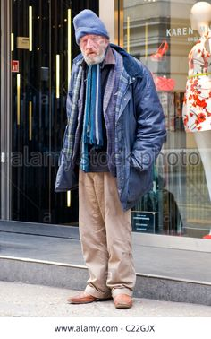 Covent Gardens , scruffy old man with grey or gray beard in woolly hat , anorak & baggy trousers by smart Karen Miller store Stock Photo