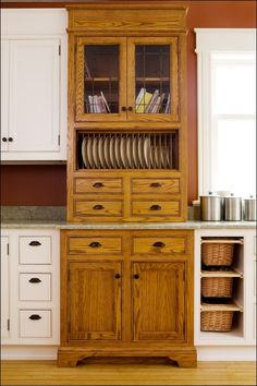 Floor to Ceiling Oak Cabinet Unit with Lead Taped Glass Doors and Plate Rack    Every kitchen has some defining feature that sticks out in a beautiful way. This floor to ceiling red oak unit with a scrolled toe accomplishes this defining feature.