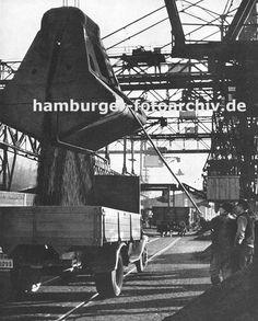 0954040 Kohlekai am Altonaer Hafen; Kräne schütten die Kohle in die bereitstehenden Lastwagen -  Hafenarbeiter dirigieren das Schüttgut mit einer langen Stange - im Hintergrund ein Güterwaggon auf den Schienen der Hamburger Hafenbahn; darüber die Förderanlage für die angelandete Kohle.