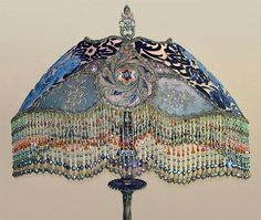#1419 SOLD  Heavy Gothic styled cast iron floor lamp with stylized gargoyles. Shade is in peacock colors of peach, green and blue and covered in metallic lace, embroidered net and beaded flowers in the small panels. The best hand beaded glass fringe with Swarovski crystals and two rare antique glass beads at the bottom of each strand.