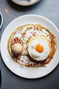 Stack of savory pancakes (topped with a fried duck egg.) Plated with a scoop of Sriracha-caramel ice cream and a scattering of candied bacon bits (over lines of maple syrup.)