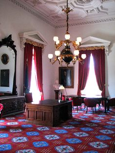 Part 1-Greek Revival/ American Empire. The interiors during this time often had tall windows with French styled drapery in fabrics such as silk, damask, or velvet. The carpet had large geometric or medallion patterns and was used from wall to wall. Common colors were saturated tones of yellow, royal blue, dark green, and crimson red. Photo credit to Don Shall. No changes were made to this image. License: https://creativecommons.org/licenses/by-nc-nd/2.0/