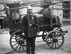 Captain Thomas Mourby with the old fire pump behind Montgomery town hall, Wales c. 1905