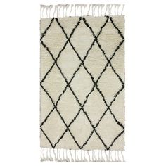 Add a pop of pattern to your living room or den with this hand-knotted wool rug, showcasing a shag design, fringe trim, and diamond trellis motif.