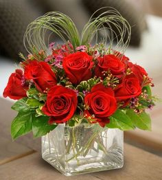 Red Roses in a cute, compact cube accented with Beargrass in a heart shape and a pretty accent flower.   Love it? We ship nationwide! @Nanz and Kraft Florists