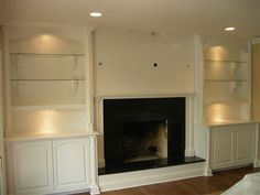 Nice use of lighting and moulding. The minimualist mantle leaves me wanting something more substantial . I'm not a fan of the glass shelves in this application. built in cabinets around fireplace Built In Around Fireplace, Tv Over Fireplace, Home Fireplace, Fireplace Remodel, Fireplace Surrounds, Fireplaces, Fireplace Hearth, Fireplace Ideas, Fireplace Update