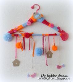 Kledinghanger bewerkt met wol, knopen, pompons enz.