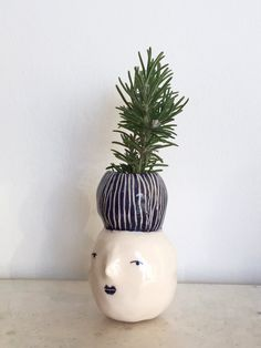 Small glazed face vase. White clay, cobalt oxide and glaze. dimensions:Length is 10'5 cm and its more wide point is 6'5.  Planted and created by: Marta Claret
