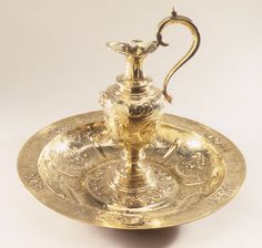 """1610-1611 English Ewer and basin at the Metropolitan Museum of Art, New York - From the curators' comments: """"The combination of ewer and basin was a refinement of life borrowed from the East in very early times, before the general use of forks made the washing of hands during a meal unnecessary. The hands were held over the basin and a server poured a stream of perfumed water over them."""""""