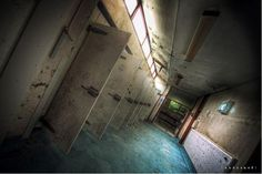 The rooms shown here may be abandoned and decaying now, but once they were places where the insides of peoples' bodies were exposed. In the row of fridges above were trays of bodies waiting to go under the pathologist's knife or stored there afterward –