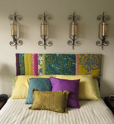 DIY upholstered headboard and I love the lanterns behind the bed on the wall
