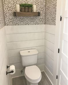 Farmhouse bathroom with half wall shiplap wainscoting and stenciled walls.
