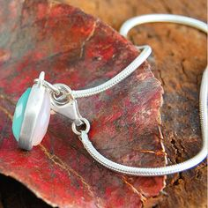 This modern handmade sterling silver tear drop charm bracelet features beautiful pink and aqua chalcedony stones hanging from a delicate jewelry vintage bangle. #Embersjewellery #Jewellery #Jewellery #accessories #Women