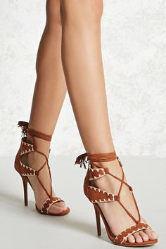 A pair of faux suede heels featuring an open toe, contrast topstitching, cutout detail, a lace-up vamp, and a tie closure with tassels. This is an independent brand and not a Forever 21 branded item.