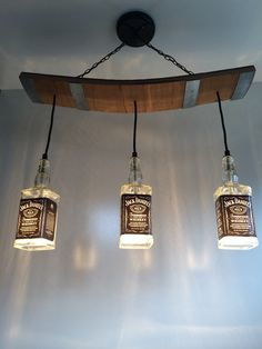 This light fixture is made from repurposed Jack Daniels bottles and wooden slats from a used barrel including the metal bands. Would be a - Diy Healthy Home Remedies Lampe Jack Daniels, Jack Daniels Bottle, Barrel Of Jack Daniels, Liquor Bottle Lights, Liquor Bottles, Bottle Lamps, Tequila Bottles, Skateboard Light, Wooden Slats