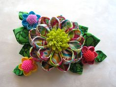 This gorgeous spring hair clip is a riot of fun colors. Shell brighten up any hairdo and add fun and whimsy to any outfit. Who doesnt love spring?  This clip measures about 4 inches across and has a focal bloom diameter of 2 1/2 inches. She is mounted on a 2 1/2 inch silver colored alligator clip. Little flowers are on armatures that can be slightly tweaked and repositioned. Please dont hesitate to contact me with questions