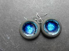 Medium to Lightweight ceramic drops with black porcelain and glass inlay crackled in the center of the drops. in dark blue and light blue. Topped with Sterling silver ear wires. These earrings measure