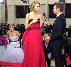 Jennifer Lawrence photobombing Taylor Swift being interviewed by Ryan Seacrest at the Golden Globes