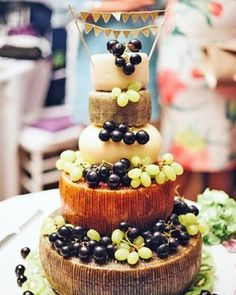 "We round up some of our favorite nontraditional wedding cakes on the site! This is a tiered cheese ""cake"" with fresh grapes from an outdoor wedding 