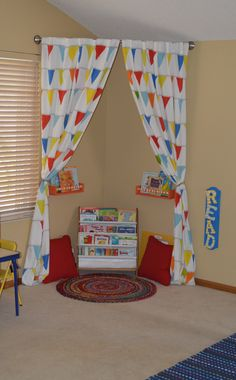 great idea for reading area in child's playroom - just hang curtain rod in the corner with some shelves, pillows, and a rug.