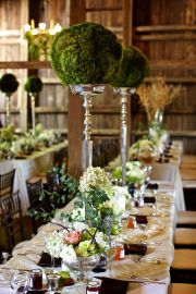 I like how the balls of greenery are placed on candle holders to make table decor