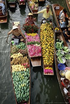 Market traders in boats selling flowers and fruit, Damnoen Saduak floating market, Bangkok, Thailand. #treasuredtravel