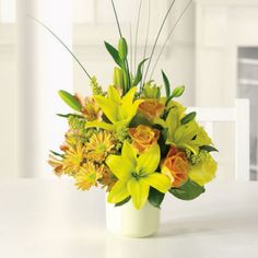 Bright-yellow lilies and fire-orange roses awaken the senses with sunny greetings for any occasion. Brighten someone's day today! *Contents may vary *Container may be substituted with one of equal value