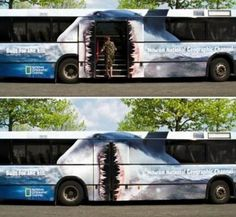 A cool bus paint job with shark teeth on the back doors. An amazing mural on this transportation vehicle. The advertisement is for the national geographic channel.