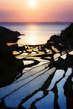These rice terraces in the southern Kyushu region of Japan, are well known to photographers. Late seasonal rains allow planting in the area to start later than other regions, the evening sun aligning with the fields reflects off the watered terraces creating a landscape of mirrors ... (Jason Amery, photographer).