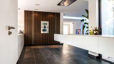 Het 4,5 meter lange zwevende keukenblad steekt ca. 1,5m de kamer in en benadrukt de lengte. De houtfineer kastenwand benadrukt de breedte.